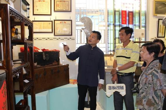 作者向懷舊物品捐贈者介紹陳列空間的西堤華人文物。
