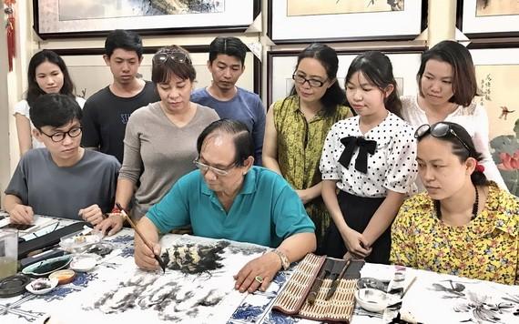 張漢明正指導學生們畫畫。