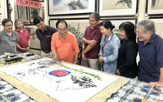張漢明(左四)與各畫家協同創作。