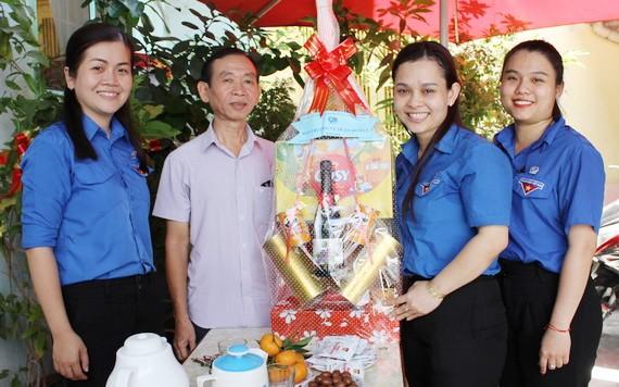 共青團第五郡郡委代表團向華人老幹部梁鴻德(左二)贈送禮物。