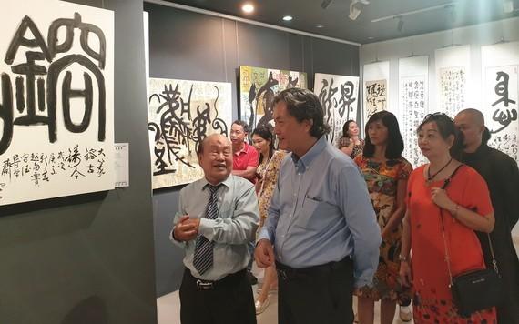 人民藝人張路書畫家(左一)向來賓介紹書法作品。