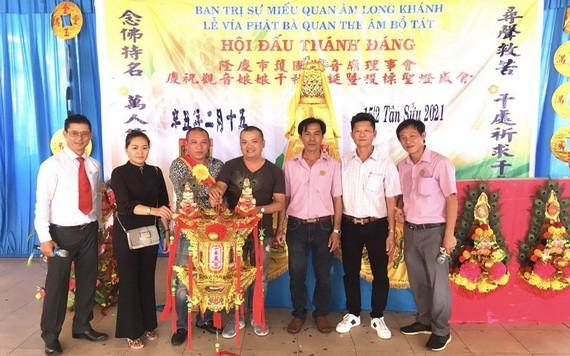 該廟理事長凌欽廷(右三)移交投得觀音慈袍給黃世英與家人。