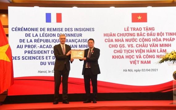 法國駐越南特命全權大使(左)向周文明教授(右)頒授北斗星勳章。(圖源:阮懷)