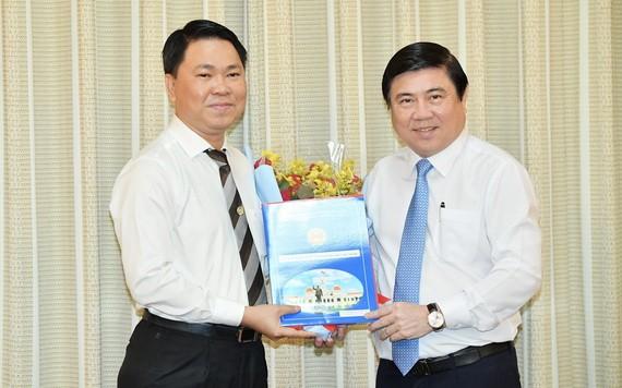 新任市建設廳長陳黃軍(左)從市人委會主席阮成鋒手中接過人事委任《決定》。(圖源:越勇)