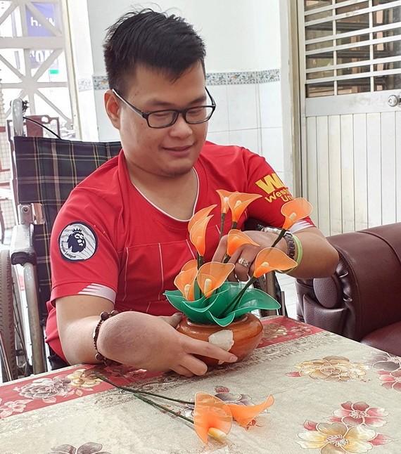 陳文雄拿著他親手做的假花。