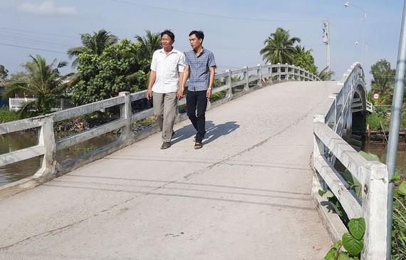 阮文俊(左)走在他捐出逾6000萬元來築的橋上。
