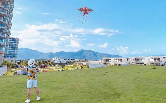 遊客在度假區海灘旁的草坪上放風箏。