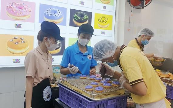 烘焙師按消費者要求製做甜甜圈。