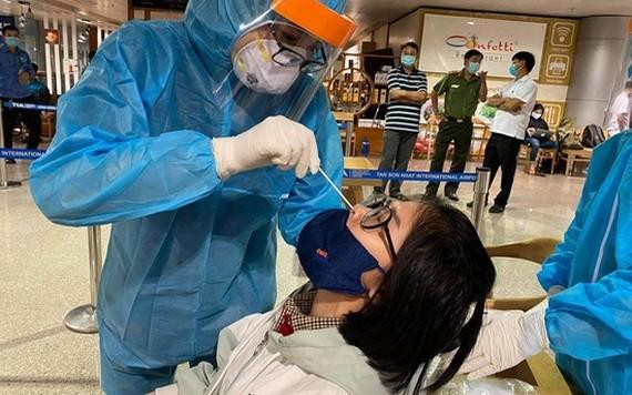 口岸防疫工作人員向一名入境者進行鼻拭子取樣測試。(圖源:VTV)