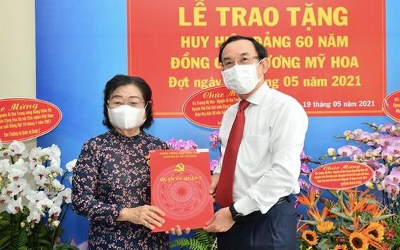 市委書記阮文年(右)向張美華同志(左)頒授60年黨齡紀念章。(圖源:越勇)