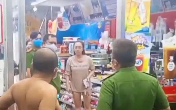 一名在公共場所不佩戴口罩的女性(中)被職能力量提醒。(圖源:視頻截圖)