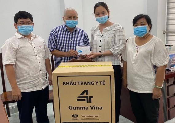 華人企業家呂永雄(左二)向第五郡第四坊領導轉交支持防疫物資。