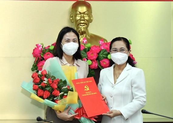范氏清賢同志(左)從市人民議會主席阮氏麗手中接過委任《決定》和祝賀鮮花。(圖源:越勇)