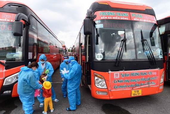民眾穿著防護服準備搭乘免費班車離開本市返回福安省。