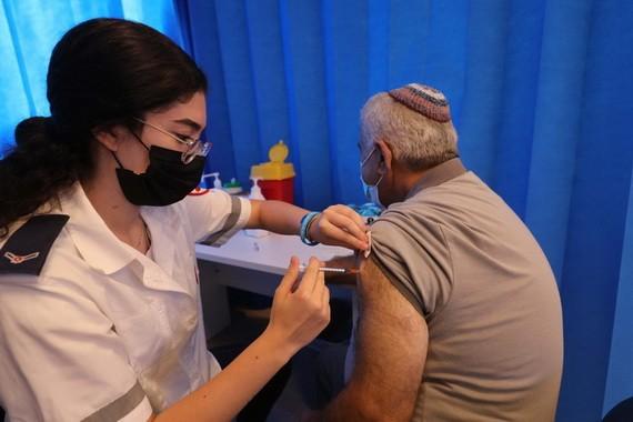 8月17日,一名男子在以色列中部城市莫迪因的一處接種點接種第三劑新冠疫苗。(圖源:新華社)