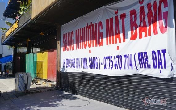 """一家商店因疫情而關門停業,門外掛著""""門面轉租""""的大橫幅。(圖源:VNN)"""