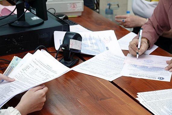 本市某所大學的學生正在辦理貸款手續。