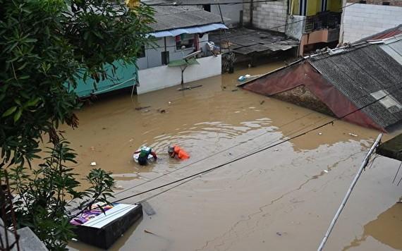 2021年2月8日,印尼雅加達,大雨造成洪水氾濫,一名居民正在撤離。 (圖源:AFP)