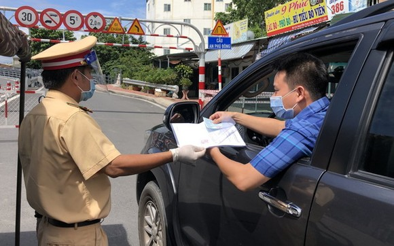 職能力量在新冠疫情防控監察站檢查司機的證件。
