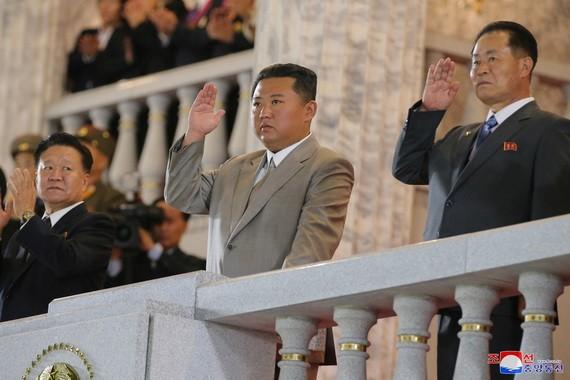 朝鮮最高領導人金正恩(中)罕見穿上一套灰色西裝出席閱兵式。(圖源:朝中社)