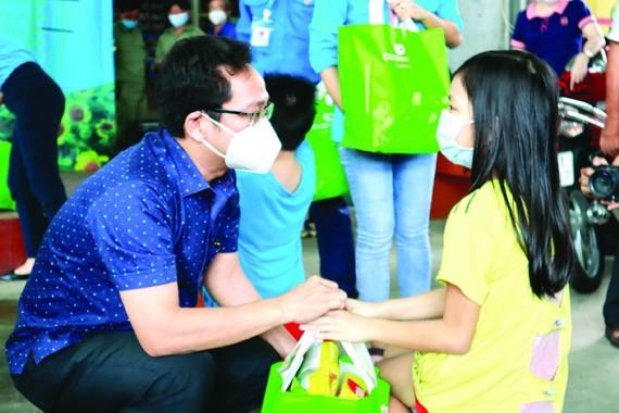 市越南祖國陣線委員會副主席范明俊向西盛坊少兒贈送禮物。