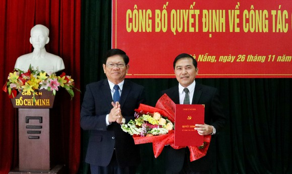 Ông Võ Công Trí, Phó Bí thư Thường trực Thành ủy Đà Nẵng trao quyết định và tặng hoa chúc mừng nhà báo Nguyễn Đức Nam