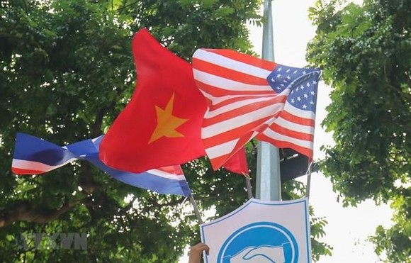 National flags of the DPRK, the US and Vietnam attached to a plaque with a friendship symbol of handshake are decorating many streets downtown Hanoi. (Photo: VNA)