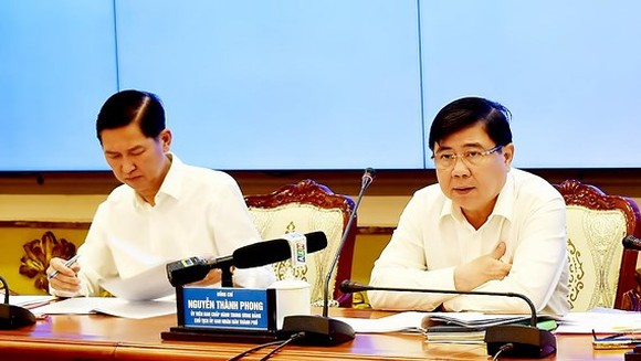 Chairman of HCMC People's Committee Nguyen Thanh Phong (R) and his deputy Tran Vinh Tuyen at the meeting (Photo: SGGP)