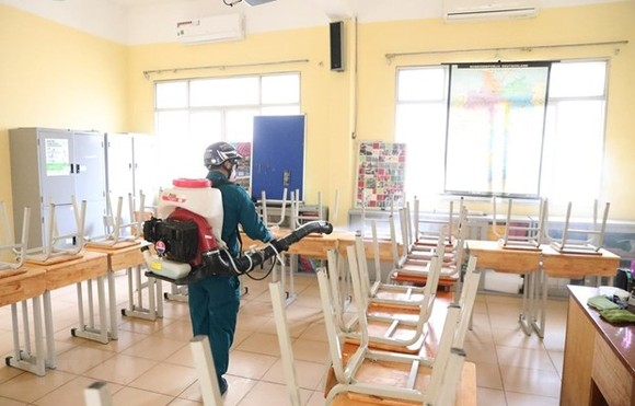 A worker sprays disinfectant at a classroom of the Viet Duc High School in Hanoi's Hoan Kiem district on February 2 (Photo: VNA)