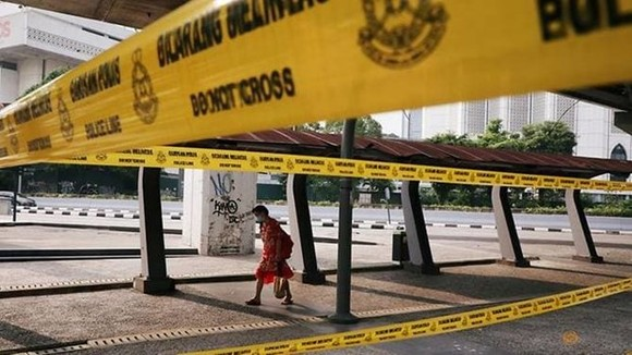 A woman wearing a protective mask walks on a street in Kuala Lumpur (Photo: Reuters)