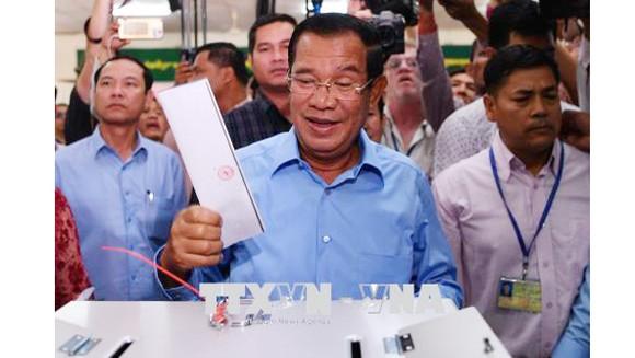 Thủ tướng Samdech Techo Hun Sen (giữa), Chủ tịch đảng Nhân dân Campuchia (CPP) cầm quyền bỏ phiếu tại điểm bầu cử ở Phnom Penh ngày 29-7. Ảnh: AFP/TTXVN