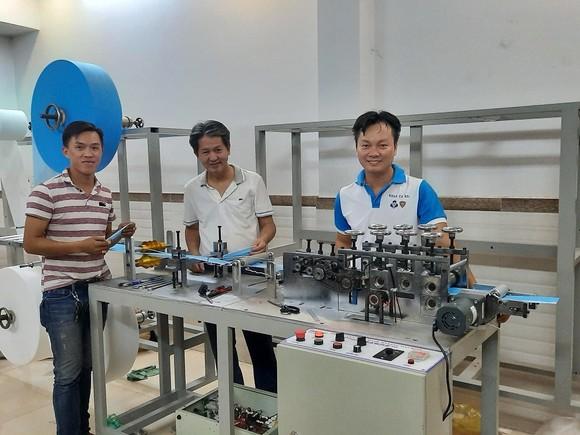 PGS.TS Nguyễn Hữu Lộc (giữa) và TS Nguyễn Thanh Hải (phải) bên máy tạo thân khẩu trang y tế.
