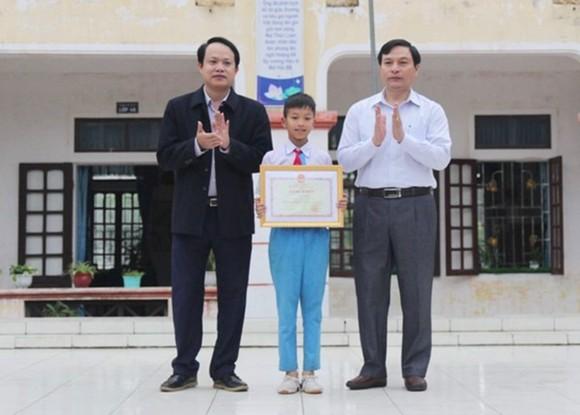 Trao bằng khen của Bộ trưởng Bộ GD-ĐT cho em Võ Hồng Hiếu. Nguồn ảnh: Phòng GD -ĐT huyện Lộc Hà