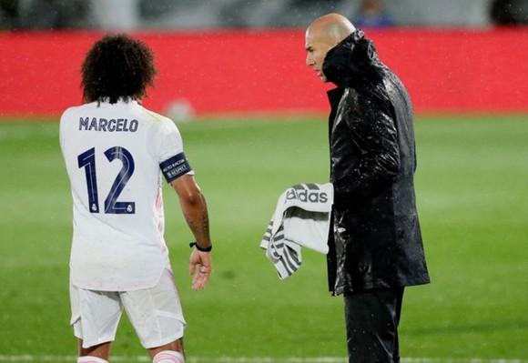 HLV Zinedine Zidane đội mưa sát cánh cùng các học trò. Ảnh: Getty Images