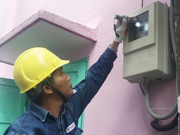 Nhân viên ngành điện kiểm tra việc lắp đặt  công tơ đo đếm từ xa mới tại nhà dân