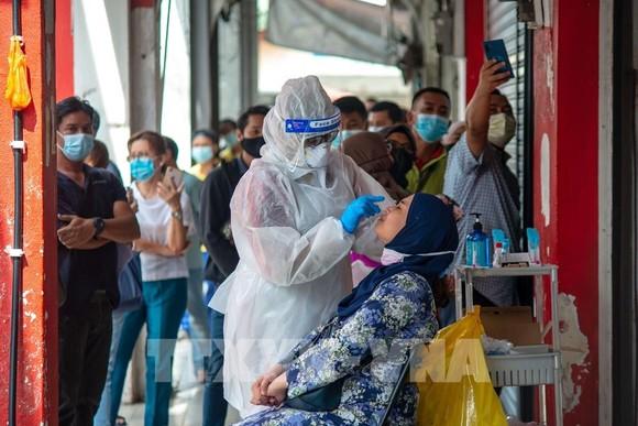 Nhân viên y tế lấy mẫu xét nghiệm COVID-19 cho người dân tại Selangor, Malaysia ngày 23-10-2020. Ảnh: THX/TTXVN