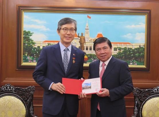 Chủ tịch Nguyễn Thành Phong trao Huy hiệu TPHCM cho ông Lim Jae Hoon. Nguồn: VOH