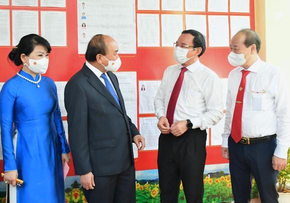 Chủ tịch nước Nguyễn Xuân Phúc trao đổi cùng Bí thư Thành ủy TPHCM Nguyễn Văn Nên sau khi bỏ phiếu. Ảnh: VIỆT DŨNG