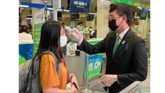 Kiểm tra thân nhiệt hành khách trước khi vào làm thủ tục lên máy bay tại sân bay Tân Sơn Nhất. Ảnh: CAO THĂNG
