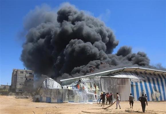 Lính cứu hỏa nỗ lực dập lửa căn nhà bị trúng oanh kích của máy bay Israel tại thành phố Rafah, Dải Gaza. (Ảnh: THX/TTXVN)