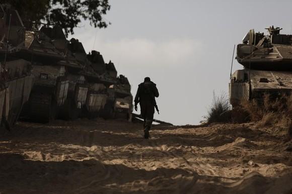 Một binh sĩ Israel đi bộ dọc theo những chiếc xe tăng hạng nặng được triển khai tới gần Dải Gaza. Ảnh: AP