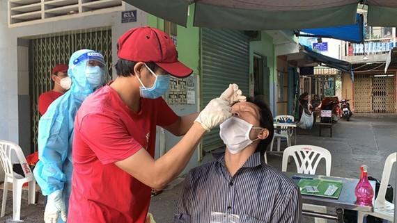 Người dân tự lấy mẫu test nhanh tại nhà sau khi được nhân viên y tế hướng dẫn.