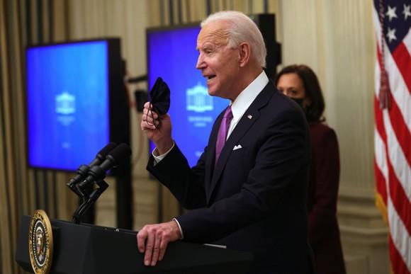 Joe Biden giơ khẩu trang khi Kamala Harris xuất hiện trong một sự kiện tại Phòng ăn Nhà nước của Nhà Trắng ngày 21 tháng 1 năm 2021 ở Washington, DC. (Ảnh của Alex Wong / Getty Images)