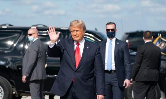 Ông Donald Trump vẫy tay chào sau khi hạ cánh xuống Sân bay Quốc tế Palm Beach ở West Palm Beach Fla., Vào ngày 20 tháng 1 năm 2021. (Alex Edelman / AFP qua Getty Images)