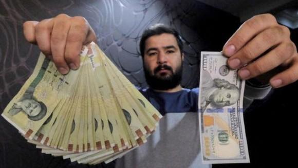Một nhà đổi tiền ở thủ đô Tehran của Iran trưng tờ 100 USD (phải) và số tiền tương ứng bằng đồng Rial hôm 20-1-2016 - Ảnh: REUTERS