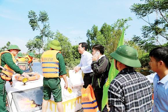 Anh Vũ Anh Tuấn (người mặc áo trắng) Phó TGĐ CPV cùng đoàn công tác của Bộ trưởng Bộ NN-PTNT trao tặng 100 suất quà tại vùng lũ huyện Lệ Thủy, tỉnh Quảng Bình