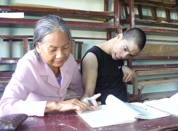 Bà giáo Nguyễn Thị Thông đang dạy cho cháu Nguyễn Văn Nguyên