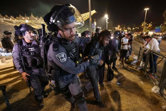 Lực lượng cảnh sát Israel bắt giữ một người Palestine. Ảnh: Reuters