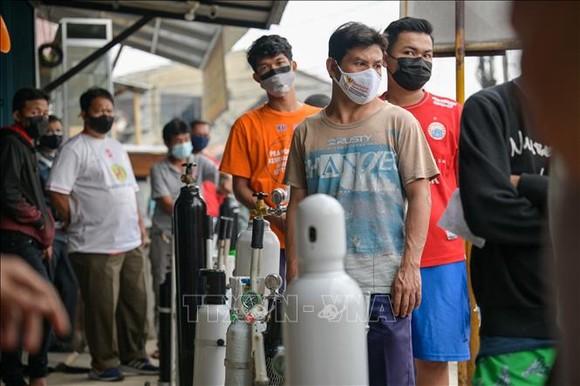 Người dân xếp hàng để nạp bình oxy tại một cửa hàng ở Jakarta, Indonesia, ngày 30-6-2021. Ảnh: AFP/TTXVN