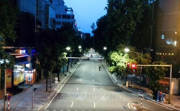 Phố Huế, quận Hai Bà Trưng thưa thớt phương tiện đi lại lúc 19 giờ ngày 24-7. Ảnh: TTXVN